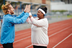 Achievement. Trainer congratulating one of his trainees on sport achievement royalty free stock image