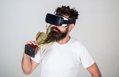 Achievement unlocked. Man bearded hipster vr headset holds golden goblet. Man winner virtual competition. Hipster. Virtual gamer got achievement. Feel victory royalty free stock photography