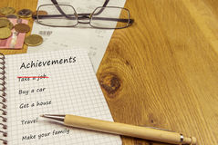 Achievements list in a spiral notebook. List of achievements written down in a spiral notebook, on a wooden desk Stock Image