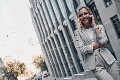 Achieving best results. Beautiful young woman in suit talking on the phone and smiling while standing outdoors stock images