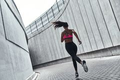 Achieving best results. Full length rear view of young woman in sports clothing jogging while exercising outdoors stock photos