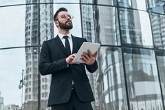 Achieving best results. Good looking young man in full suit using digital tablet while standing outdoors stock image