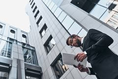 Achieving best results. Low angle view of handsome young man in full suit reading contract while standing outdoors royalty free stock images
