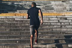 Achieving best results. Rear view of young African man in sports clothing running up the stairs while exercising outdoors royalty free stock images