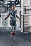 Achieving best results. Full length of young African man in spor. T clothing skipping rope while exercising in the gym Stock Photo