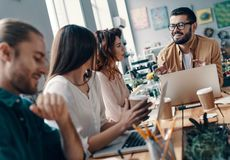 Achieving best results together. Group of young modern people in smart casual wear discussing something and smiling while working in the creative office stock image