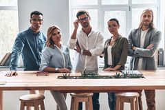 Achieving best results together. Group of young modern people in smart casual wear looking at camera and smiling while working in the creative office stock image
