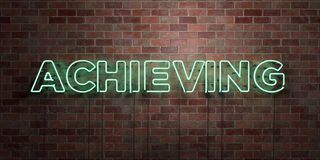 ACHIEVING - fluorescent Neon tube Sign on brickwork - Front view - 3D rendered royalty free stock picture Stock Images