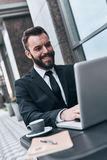 Achieving great results. Good looking young man in full suit using computer and smiling while sitting in the cafe outdoors royalty free stock images