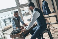Achieving success as a designer. Young fashionable designer choosing fabric with his client while sitting in the workshop royalty free stock photo