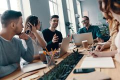 Achieving success together. Group of young modern people in smart casual wear discussing something and smiling while working in the creative office royalty free stock images