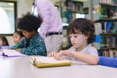 AChildern die in een bibliotheek bestuderen stock foto