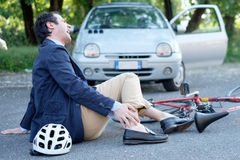 Aching man after bicycle accident. On the asphalt Stock Photos