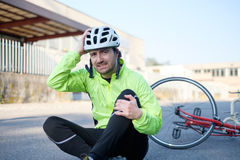 Aching man after bicycle accident. On the asphalt Royalty Free Stock Image