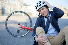 Aching man after bicycle accident. On the asphalt Royalty Free Stock Images