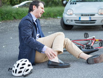 Aching man after bicycle accident. On the asphalt Stock Photo