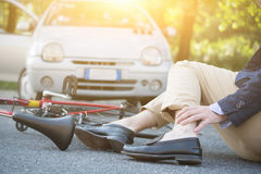 Aching man after bicycle accident. On the asphalt Royalty Free Stock Photography