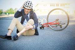 Aching man after bicycle accident. On the asphalt Royalty Free Stock Photos