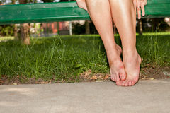 Aching tired feet. Female aching feet with redness on the ground royalty free stock photos