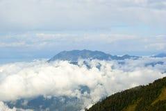 Achishkho山的看法在从通行证Bzerpinsky檐口的高加索,耸立在云彩上 免版税库存图片