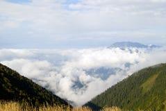 Achishkho山的看法在从通行证Bzerpinsky檐口的高加索,耸立在云彩上 免版税库存照片