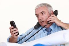 Achitect getting multiple calls. Senior architect getting multiple calls Royalty Free Stock Photography