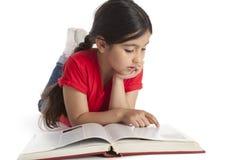 Acht éénjarigenmeisje dat een boek leest Stock Foto