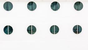 Acht Öffnungen auf weißer Schutzwand Stockbilder