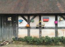 Acht bunte hölzerne Vogelhäuser, die an einer großen Gartenhalle hängen Stockfotografie