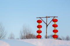 Acht chinesische Laternen auf einem Schneehügel Stockbild