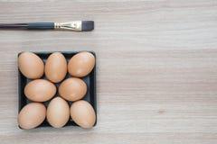 Acht Eier in der Platte des schwarzen Quadrats mit einer Bürste auf Holzoberfläche Stockfotos
