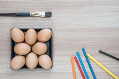 Acht Eier in der Platte des schwarzen Quadrats mit einer Bürste und Farbbleistiften Lizenzfreie Stockbilder