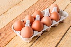 Acht Eier im Kasten auf einem Holztisch Stockbilder