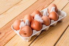 Acht Eier im Kasten auf einem Holztisch Lizenzfreies Stockfoto