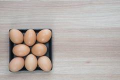 Acht Eier im Schwarzblech auf Holzoberfläche mit Raum für Text Lizenzfreies Stockbild