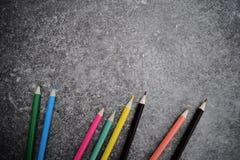 Acht Farbbleistifte auf grauem Hintergrund Lizenzfreie Stockbilder