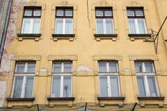 Acht Fenster auf der Fassade des alten schäbigen gelben Hauses Stockfoto