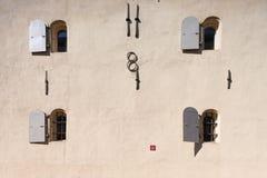Acht Fenster auf der Wand eines mittelalterlichen Hauses Stockbild