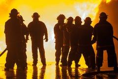 Acht Feuerwehrmänner während der Feuerbekämpfungsübung Stockbild