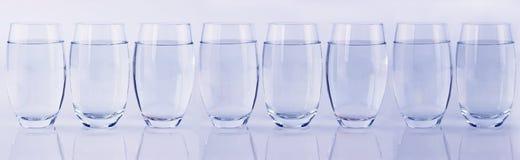 Acht Gläser Wasser in einer Reihe Stockbild