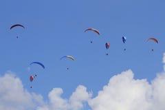 Acht Gleitschirme, die gegen den blauen Himmel fliegen Stockfotografie