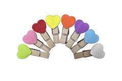 Acht houten klemmen met kleurrijke harten stock fotografie