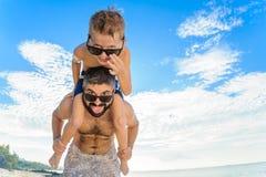 Acht Jahre alte Junge, die auf Vati ` s sitzen, schultert Beide in den Schwimmenkurzen hosen und -Sonnenbrille, Spaß auf dem Stra Lizenzfreie Stockfotos