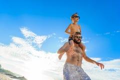 Acht Jahre alte Junge, die auf Vati ` s sitzen, schultert Beide in den Schwimmenkurzen hosen und -Sonnenbrille, Spaß auf dem Stra Stockfotos