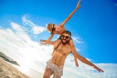 Acht Jahre alte Junge, die auf Vati ` s sitzen, schultert Beide in den Schwimmenkurzen hosen und -Sonnenbrille, Spaß auf dem Stra Lizenzfreie Stockfotografie