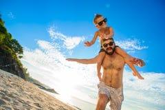 Acht Jahre alte Junge, die auf Vati ` s sitzen, schultert Beide in den Schwimmenkurzen hosen und -Sonnenbrille, Spaß auf dem Stra Lizenzfreies Stockfoto