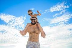 Acht Jahre alte Junge, die auf Vati ` s sitzen, schultert Beide in den Schwimmenkurzen hosen und -Sonnenbrille, Spaß auf dem Stra Stockbilder