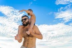 Acht Jahre alte Junge, die auf Vati ` s sitzen, schultert Beide in den Schwimmenkurzen hosen und -Sonnenbrille, Spaß auf dem Stra Stockfotografie