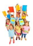Acht Jahre alte Kinder, die Lehrbücher anheben Stockfotos