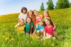 Acht Kinder, die zusammen auf dem grünen Gras sitzen Stockfoto